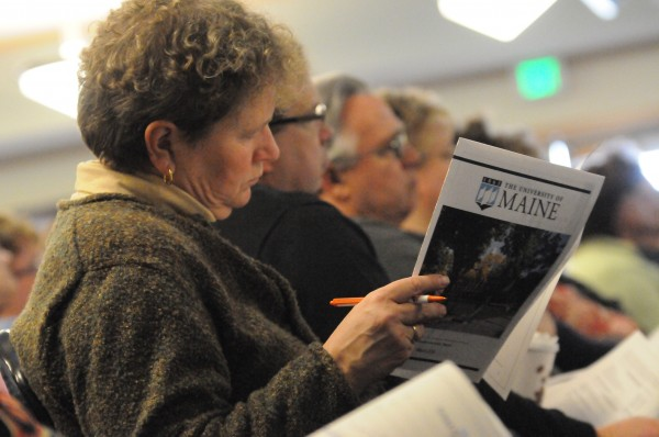 A staff member attending a meeting on the UMaine budget reads an overview of the budget shortfall unveiled in a presentation by university leaders on Friday.
