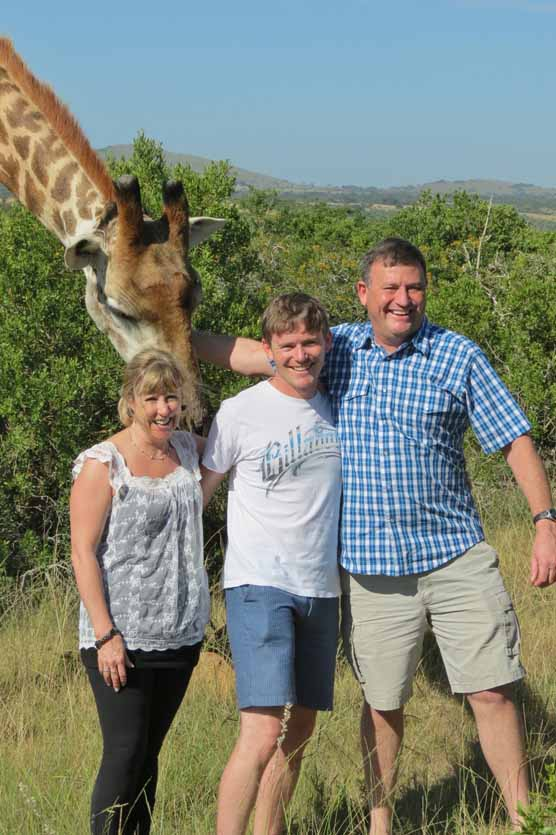 Rev. Rogan Taylor, his wife, Caroline, and son Brett had a good laugh while he pets a friendly giraffe during a recent visit to South Africa. Taylor is the new pastor at the Abbot Evangelical Free Church.