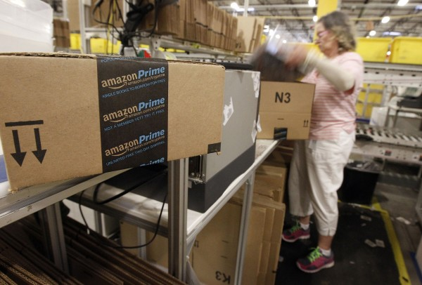 A worker prepares an item for Amazon Prime delivery at Amazon's distribution center in Phoenix, Ariz., on Nov. 22, 2013.