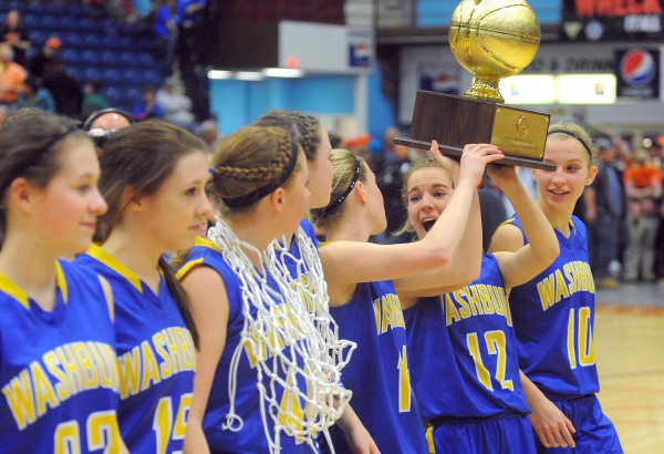 Washburn High School players hold the championship trophy after defeating Forest Hills Consolidated School in the Class D girls state championship game at the Augusta Civic Center on Saturday.