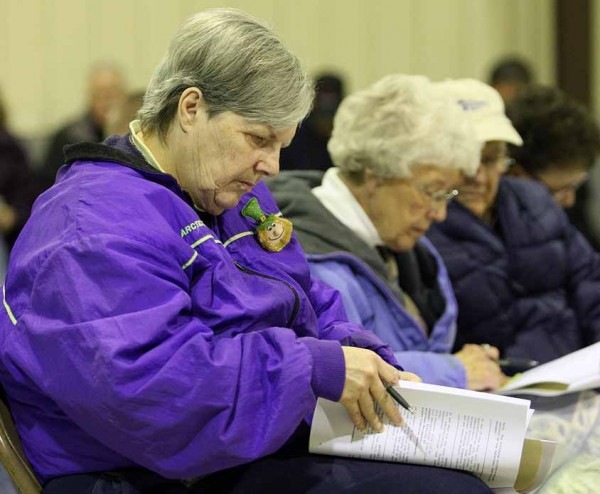 Island Falls resident Barbara Sleeper reviews the town report at Saturday's annual meeting.