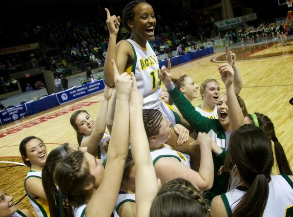The Catherine McAuley High School basketball team hoists Pamela Mukiza aloft after winning the state Class A championship in Portland on Saturday