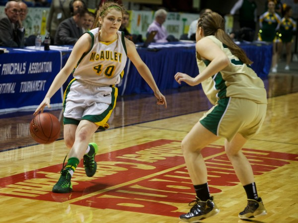 Team co-captain Jaclyn Welch dribbles down court at the Class A state championship basketball game in Portland on Saturday. The McAuley Lions went on to beat the Vikings of Oxford Hills Comprehensive High School.