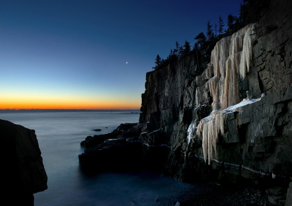 Like a frozen waterfall, a four-story high wall of ice clings to the rocks near Otter Point in Acadia National Park at dawn.
