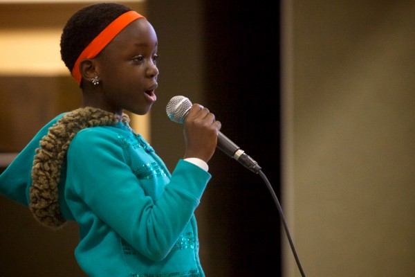 Peace Muwanguzi, 9, sings onstage with the African Children's Choir at the East End Community School in Portland on Monday. The choir had just finished a two-day run at Merrill Auditorium and will be headed for the United Kingdom in a few weeks, continuing their tour.