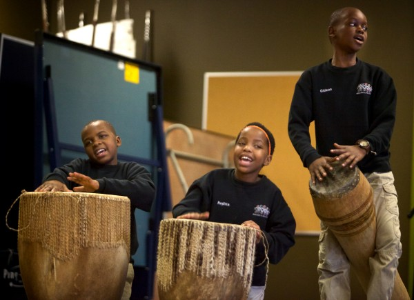 Drummers Joshua Bugembe, 9, (left), Nanditta Esther, 10, (center), and Gideon Mugonyi, 10, perform with the African Children's Choir at the East End Community School in Portland on Monday. Choir members also had the change to mingle and play with members of the East End glee club.
