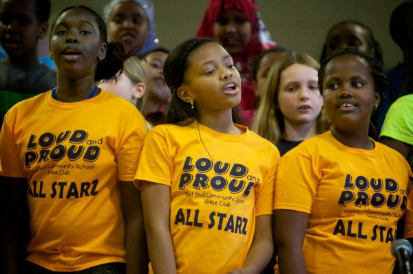 East End Community School Glee Club members (from left) Margaret Ojut, 10, Aalliyah Ferreira, 10, and Kenia Rwigema, 10, sing with their classmates at a school assembly on Monday in Portland. The glee club was hosting a performance by the African Children's Choir.