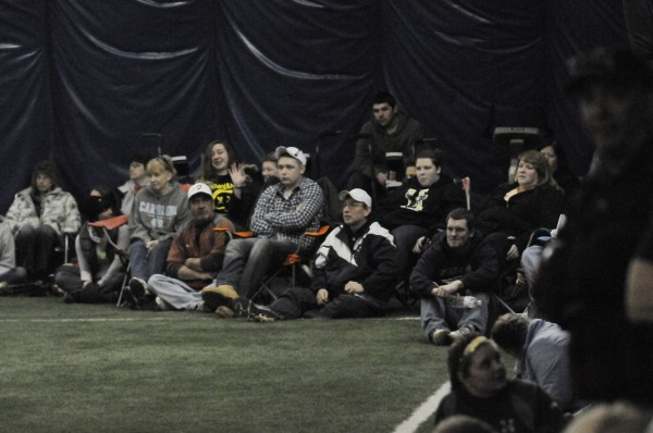 Softball spectators bring their own chairs and sit in the corner as Husson University plays Brandeis University on Saturday at UMaine's Mahaney Dome in Orono.