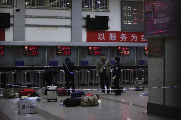 Police stand near luggages left at the ticket office after a group of armed men attacked people at Kunming railway station, Yunnan province, March 2, 2014, local time. At least 28 people have been killed in the violent attack at the train station in Kunming carried out by a group of unidentified people brandishing knives, the Chinese state news agency Xinhua said.