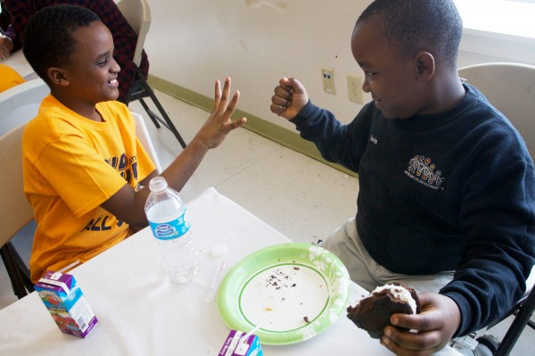 Van Chabent Ishimwe, 11, of the East End Community School Glee Club (left) plays rock, paper scissors with Kevin Mwebe, 8, of the African Children's Choir on Monday during a lunchtime mixer.