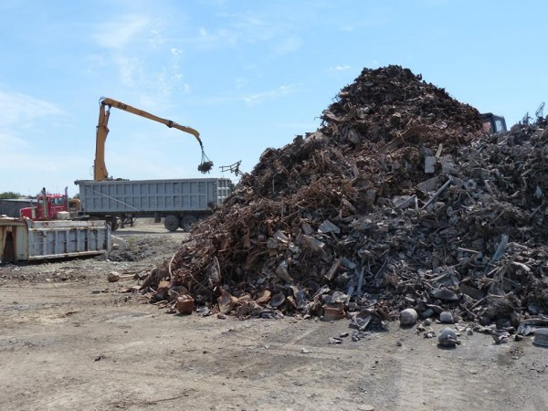 In this March 2013 file photo, waste sits in piles at ecomaine's southern Maine landfill while a magnet on a crane pulls metals from the processed refuse in the background.
