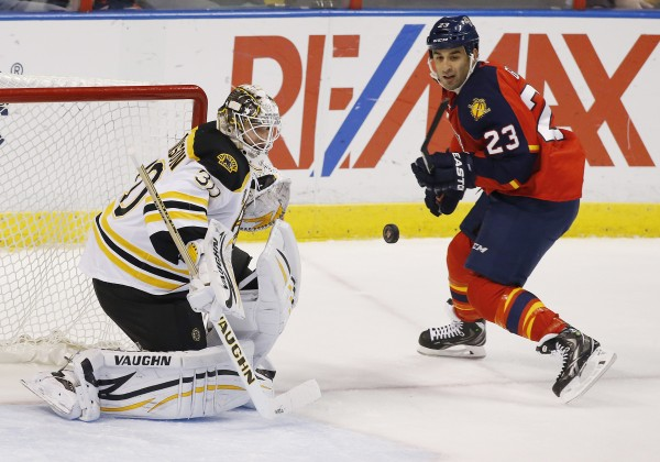 Boston Bruins goalie Chad Johnson (30) makes a save as Florida Panthers center Scott Gomez (23) looks on in the first period Sunday night in Sunrise, Fla.
