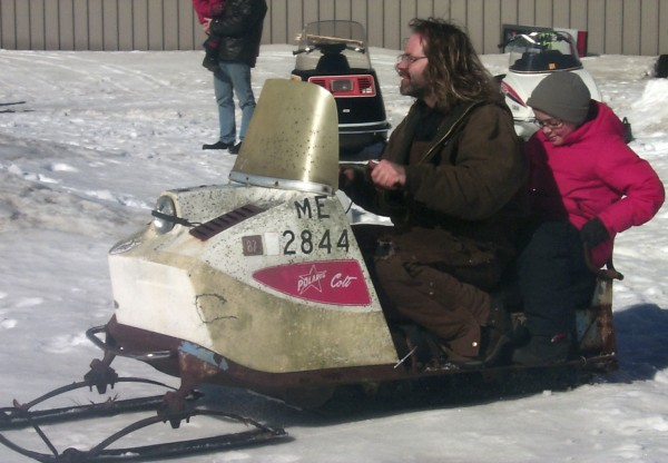 Allen &quotHigmo'' Higgins of Brunswick gives Tyler Bilodeau, 10, of Rockport a ride on his 1965 Polaris Colt snowmobile during the 2009 WinterFest at the Owls Head Transportation Museum.