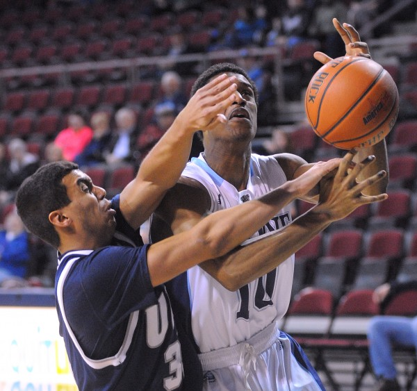 The University of Maine's Shaun Lawton (right) is fouled by New Hampshire's Daniel Dion as he moves to the basket during an America East matchup Sunday at the Cross Insurance Center in Bangor Sunday.