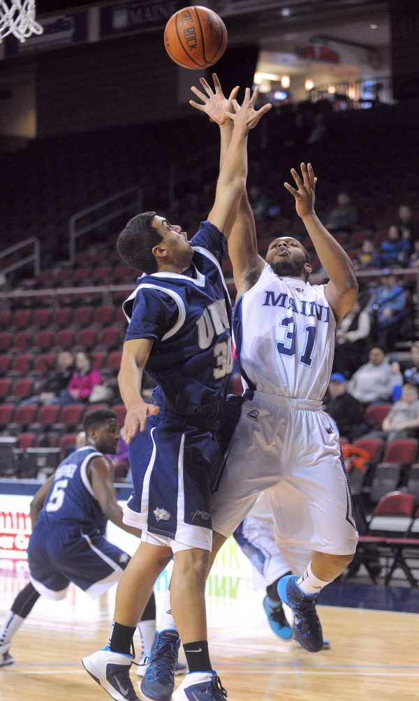 The University of Maine's Troy Reid-Knight goes up for a shot over New Hampshire's Daniel Dion during America East action Sunday at the Cross Insurance Center in Bangor.