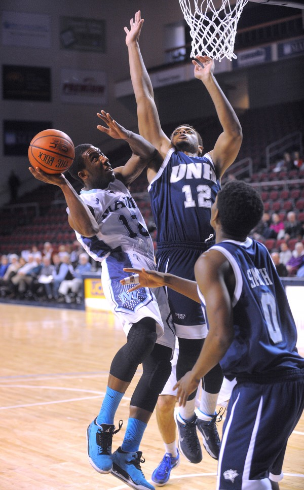 The University of Maine's Xavier Pollard (left) tries to put up a shot between New Hampshire's Jaleen Smith (right) and Frank Okeke during an America East game Sunday at the Cross Insurance Center in Bangor.
