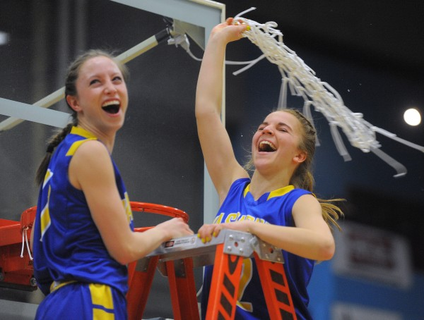 Washburn High School players Carsyn Koch (left) and Carmen Bragg cut one of the nets after defeating Forest Hills Consolidated School in the Class D girls state championship game 78-40 at the Augusta Civic Center on Saturday.