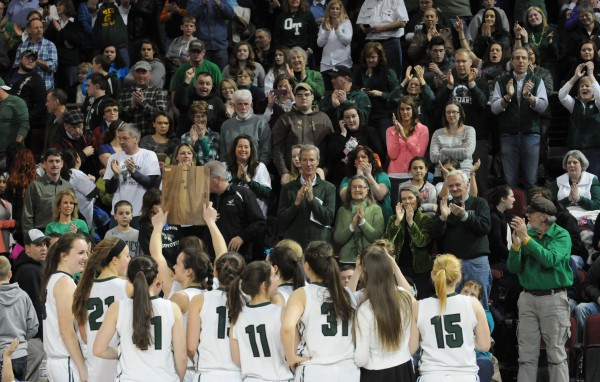 The MDI girls basketball team holds their runner-up trophy for their fans to see after losing to Lake Region 56-47 during the Class B state championship game on Friday night at the Cross Insurance Center in Bangor.
