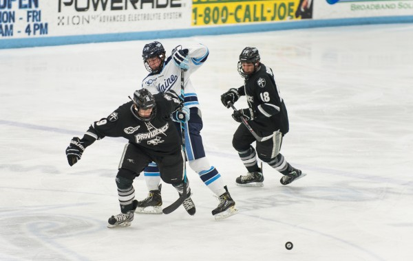 The University of Maine's Brady Campbell (center) fights for control of the puck against Providence College's Trevor Mingola (left) and Nick Saracino Friday night at the Alfond Arena.