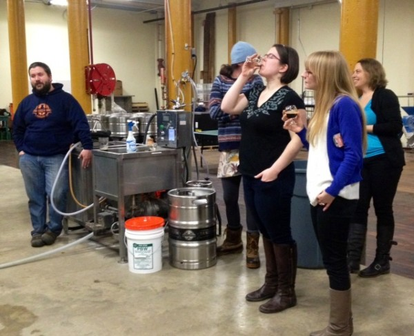 Members of Maine Beer Mavens tour Banded Horn Brewery last week. Owner Ron Graves, left looks on.