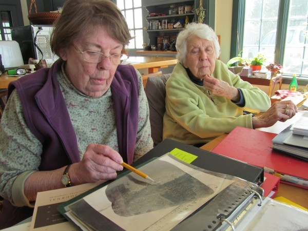 Sue Carlson (left) and Roslyn Strong look over a photograph of one of the stones found near Phippsburg's Spirit Pond in 1971. Carlson and Strong are members of the New England Antiquities Research Association and believe inscriptions carved into the stones could be signs of an early 15th century Norse voyage to Maine.