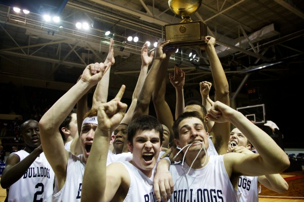 The Portland High School Bulldogs celebrate their 54-40 victory over the Hampden Academy Broncos in the Class A state basketball championship at the Cumberland County Civic Center in Portland on Saturday night.