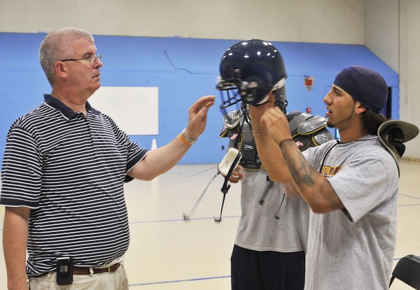 UMaine athletic equipment manager Steve Jones (left) helps Black Bears cornerback Dom Cusano get the proper helmet fit in 2009. Cusano died on Sunday.