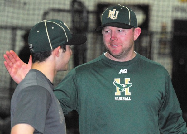 Husson University baseball coach Jason Harvey greets team member Nate Stewart during practice at Sluggers in Brewer on Wednesday night.