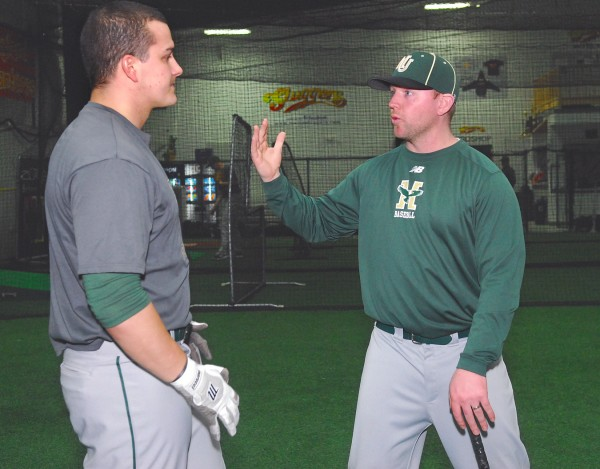 Husson University baseball coach Jason Harvey (right) gives some pointers about the game to team member Josh Gaudette during practice at Sluggers in Brewer on Wednesday night.