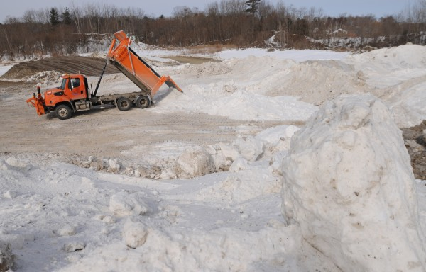 City of Bangor public workers dump truckloads of snow  from the streets and public parking lots of Bangor at a pit in Hampden on Wednesday. Workers on scene say it might take until June for the compacted ice and snow to melt.