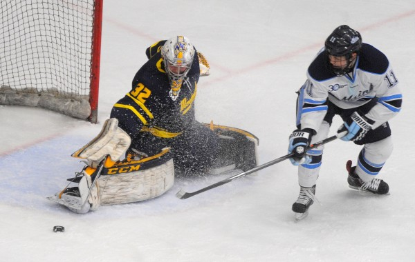 Merrimack College's Rasmus Tirronen (left) makes a save on a shot by the University of Maine's Steven Swavely during a Hockey East first-round playoff game Saturday evening at Alfond Arena in Orono. Maine won and advanced to a quarterfinal series at Providence College.