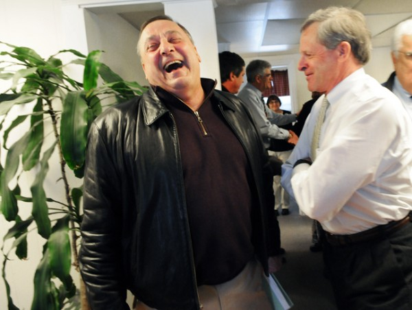 Maine Gov. Paul LePage (left) laughs at a joke by Jeffrey Cole, a partner at Cole Harrison Insurance on Main Street in Kennebunk, during his visit in the town on Friday.