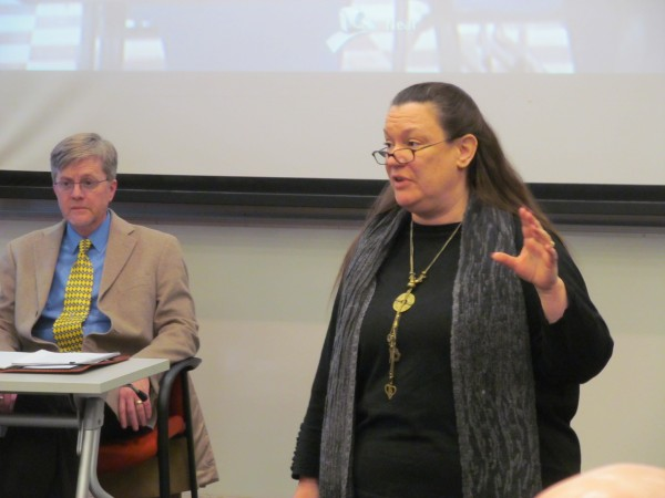 University of Southern Maine's Tara Coste, serving as chairwoman of the school's Faculty Senate, addresses attendees at the panel's Friday afternoon meeting at the Portland campus.