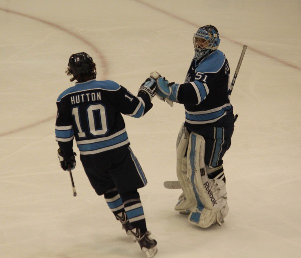 Maine goalie Martin Ouellette congratulates Ben Hutton after his second-period goal against Providence Friday night during Hockey East playoff action at Schneider Arena in Providence, R.I.