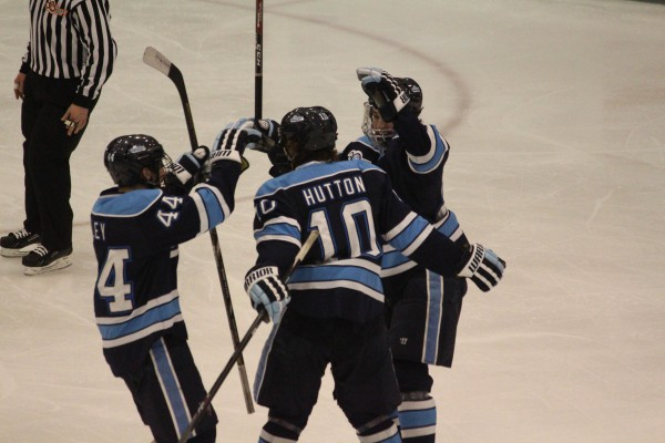 Maine's Ben Hutton (center) celebrates with two teammates after scoring a second-period goal against Providence during Hockey East playoff action Friday night at Schneider Arena in Providence, R.I.