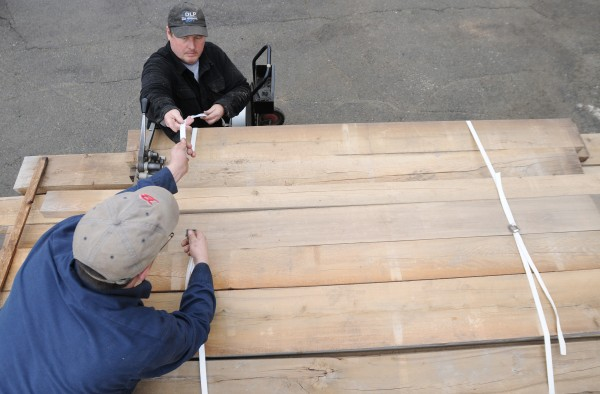Bill Stanley (left) and Jack Scott, both employees with Maine Heritage Timber, load dried wood from a kiln at the University of Maine onto a flatbed for transport to Millinocket where it will be turned into custom furniture.