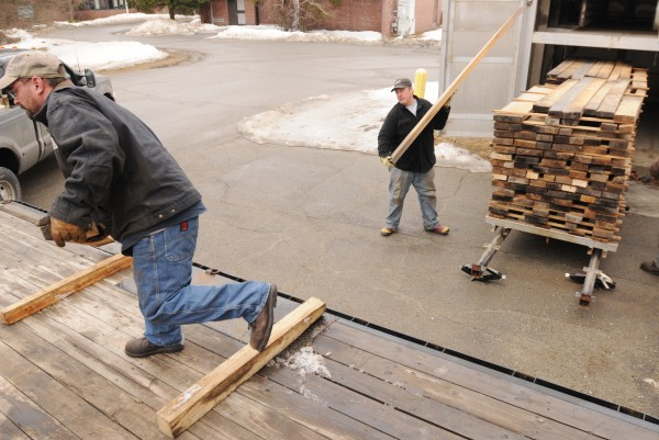 Maine Heritage Timber employees Bill Stanley (left) and Jack Scott load dried wood from a kiln at the University of Maine onto a flatbed for transport to Millinocket where it will be turned into custom furniture.
