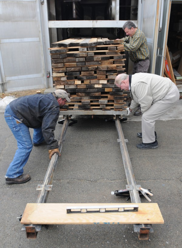 Robert Rice (right), professor of wood science at the University of Maine, Tom Shafer (background), owner of Maine Heritage Timber, and Shafer's employee Bill Stanley slide wood that has been submerged in Quakish Lake in Millinocket since the early 1800s from a small kiln run by Rice at the University of Maine on Wednesday.