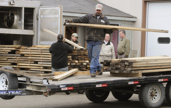 Bill Stanley, an employee with Maine Heritage Timber, loads dried wood from a kiln at the University of Maine onto a flatbed for transport to Millinocket where it will be turned into custom furniture.