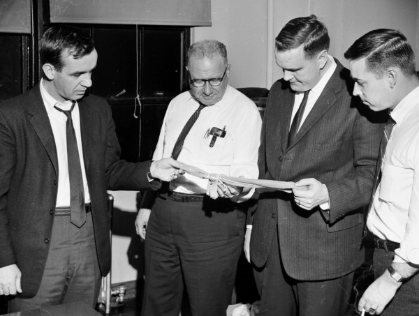 Examining the stockings found around Effie MacDonald's neck at the Bangor House on March 18, 1965, were (from left) County Attorney Howard M. Foley, Detective Captain Clifton E. Sloan, Detective Sgt. James Scripture and Assistant County Attorney Albert Blanchard Jr.