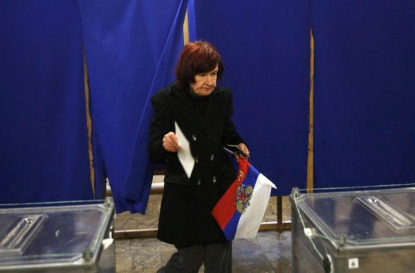 A woman holds a Russian flag as she prepares to cast her ballot during a referendum on the status of Ukraine's Crimea region at a polling station in Sevastopol, Ukraine, on Sunday. Voting got underway in Crimea on Sunday as the inhabitants of this Ukrainian region began to cast their ballots in the referendum aimed at deciding whether the peninsula leaves Ukraine and becomes part of Russia.