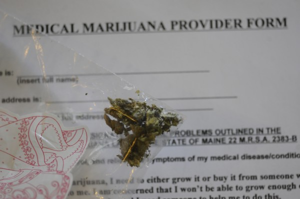 A small bag of marijuana rests on top of a medical marijuana provider form in Pittsfield in 2010.  A state judge has ruled that the Maine Department of Health and Human Services can impose fees on people who provide medicinal marijuana.