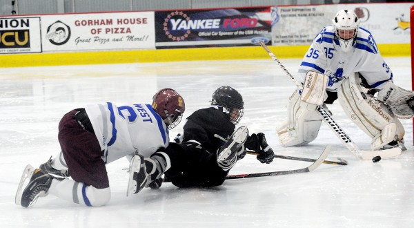 Cape Elizabeth's Dennis Frank (left) and  John Bapst's Matt Spear end up on the ice as Spear tries to get the puck past goalie Kevin Hare also from Cape Elizabeth in the first period of the Class B Winter Classic on Saturday at the University of Southern Maine Ice Arena in Gorham.