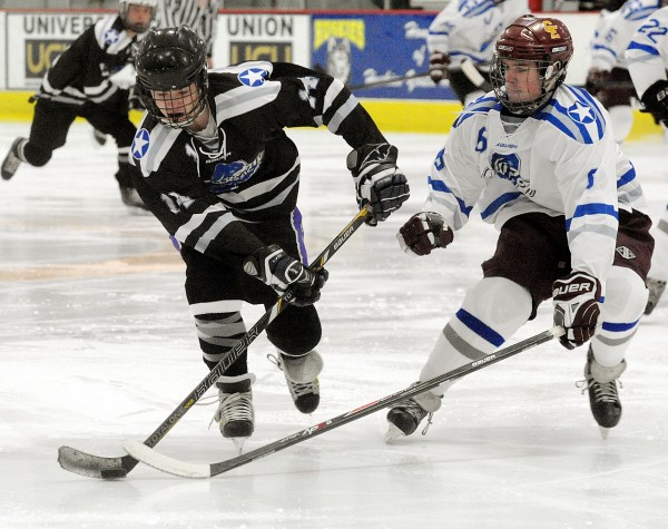 Cape Elizabeth's Dennis Frank (right) tries to get the puck from John Bapst's Matt Spear in the first period of the Class B Winter Classic on Saturday at the University of Southern Maine Ice Arena in Gorham.