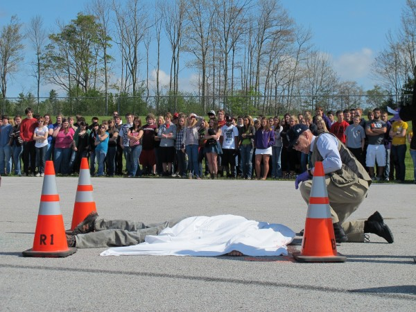 Ed David, deputy chief with the Maine State Medical Examiner's Office, investigates one of the supposed victims of a mock car accident staged at Bucksport High School on Thursday, May 17, 2012.