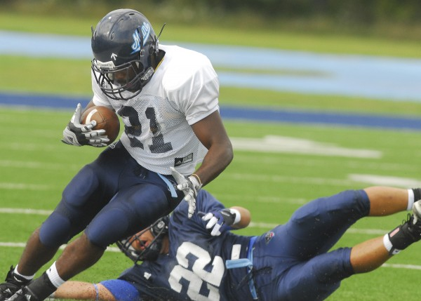 In this August 2012 photo, Maine's Zedric Joseph (left) looks for a way past the tackle of teammate Michael Mangiarelli during an intrasquad scrimmage in Orono.