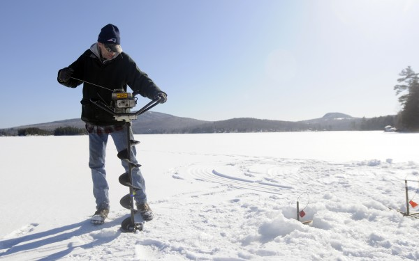 Dwight Engelhardt of Bangor drills holes in the ice on Phillips Lake in Dedham as he spends Friday, March 14 trying to catch a salmon for his dinner.