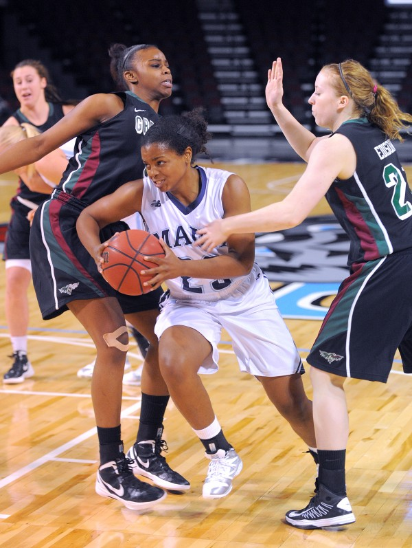 In this November 2013 file photo, Maine's Ashleigh Roberts (center) drives to the basket between Green Bay's Breannah Ranger (left) and Ellen Edison during the game at the Cross Insurance Center in Bangor.