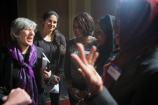 Dr. Sima Samar (left), a renowned Afghan human rights and women's rights advocate, speaks with students at Deering High School in Portland Tuesday morning following a panel discussion. The students (from left) are Neilab Habibzai, Aubine Ntibandetse, Maryan Isack and Halima Noor.