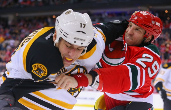 Milan Lucic of Boston (left) and New Jersey's Ryane Clowe mix it up during the first period of Tuesday night's NHL game at the Prudential Center in Newark, N.J. The Bruins won 4-2.